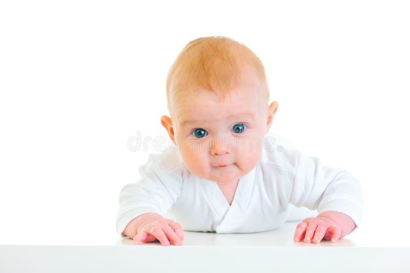 Geinteresseerde oude baby die van vier maanden op buik legt royalty-vrije stock afbeelding