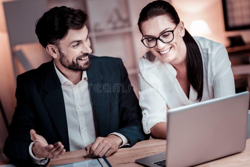 Geinteresseerde verantwoordelijke collega's die en laptop glimlachen met behulp van royalty-vrije stock afbeeldingen