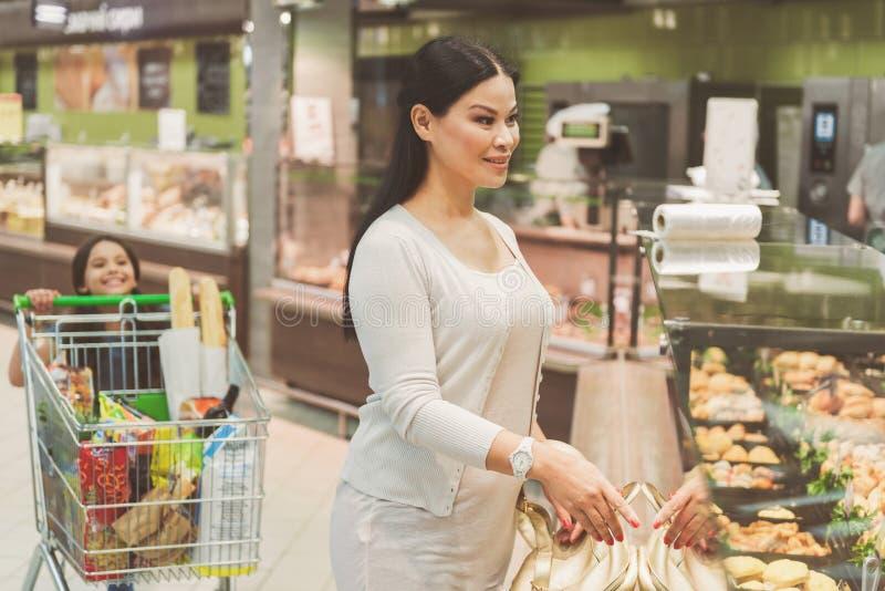 Geinteresseerde vrouw die voedsel gaan kopen royalty-vrije stock foto