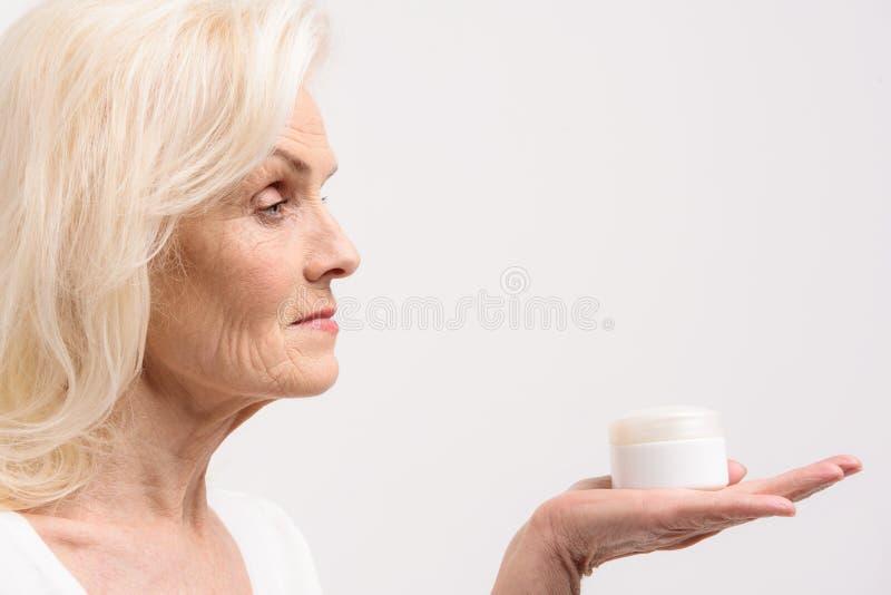 Geinteresseerde vrouw die witte kruik met vochtinbrengende crème houden royalty-vrije stock foto