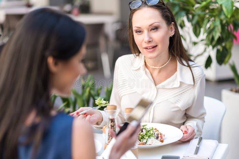 Geinteresseerde vrouwen proevende salade in koffie stock afbeeldingen