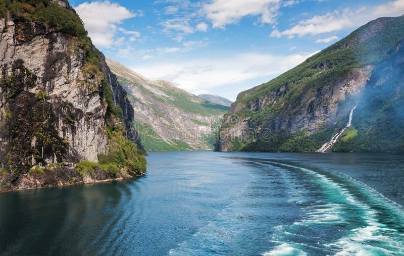 Geiranger海湾、七个姐妹瀑布和在水的小船足迹的图象 图库摄影