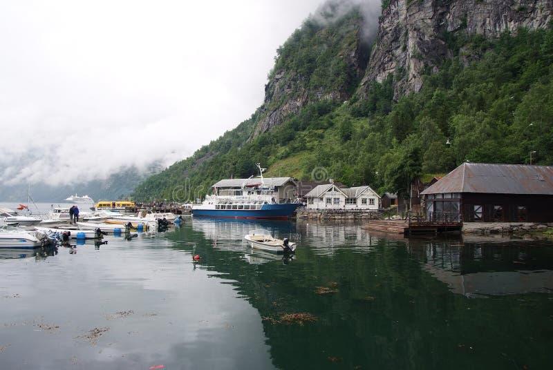 Geiranger, Norvegia - 25 gennaio 2010: le case del villaggio, barche nel porto del mare sulla montagna abbelliscono Trasporto del fotografie stock libere da diritti