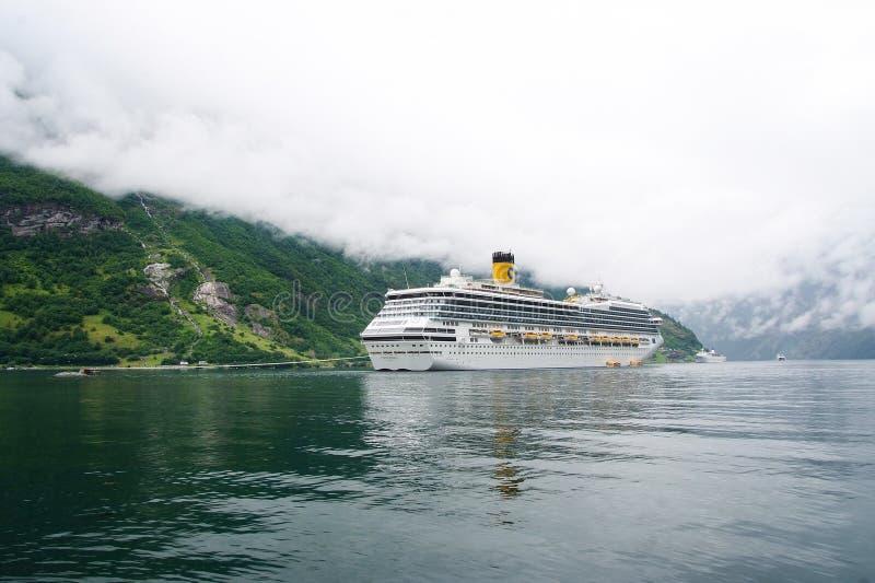 Geiranger, Norvegia - 25 gennaio 2010: nave da crociera in fiordo norvegese Fodera di passeggero messa in bacino in porto Destina fotografie stock libere da diritti