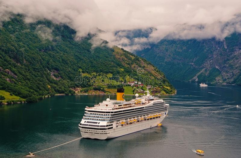 Adventure, discovery, journey. Cruise ship in norwegian fjord. Passenger liner docked in port. Travel destination. Geiranger, Norway - January 25, 2010 stock photo