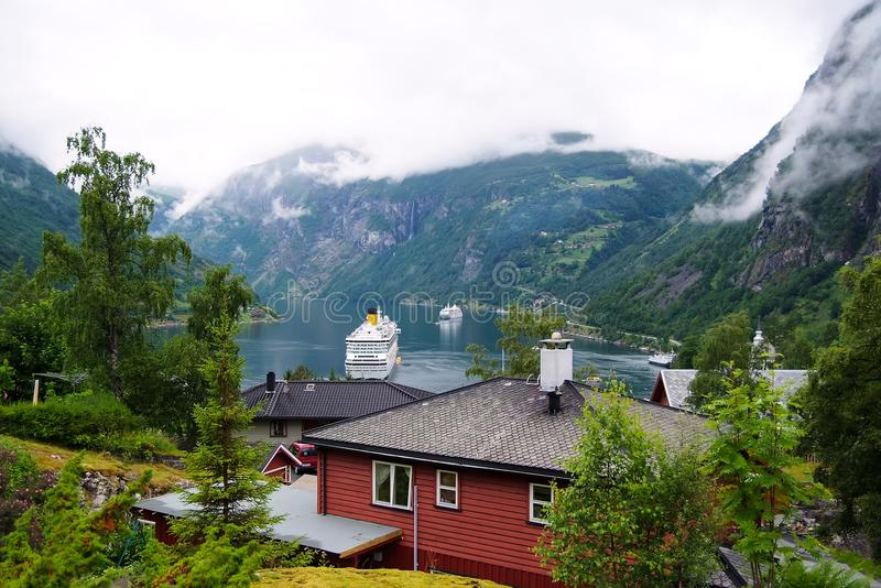 Geiranger, Norway - January 25, 2010: adventure, discovery, journey. Ship in norwegian fjord on cloudy sky. Ocean liner in village royalty free stock photography