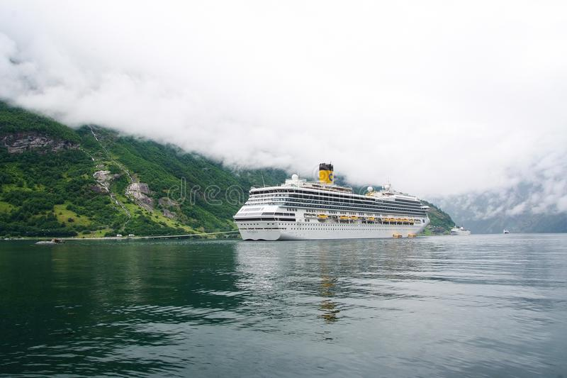 Geiranger, Norway - January 25, 2010: cruise ship in norwegian fjord. Passenger liner docked in port. Travel destination, tourism. royalty free stock photos