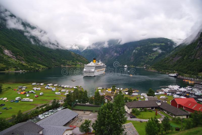 Geiranger, Norway - January 25, 2010: vacation, trip, wanderlust. Ship in norwegian fjord on cloudy sky. Ocean liner in village ha royalty free stock photography
