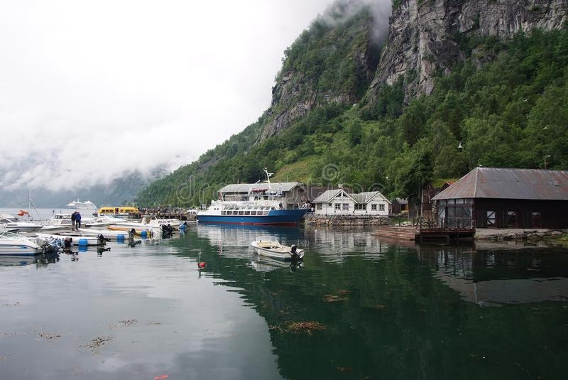 Geiranger, Norway - January 25, 2010: village houses, boats in sea harbor on mountain landscape. Water transport, vessels. Travel royalty free stock photos