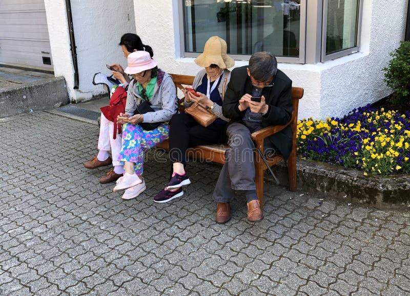 GEIRANGER, NORWEGIA - 15-June-2019: Seniory na drewnianej ławce używać mądrze telefony fotografia stock