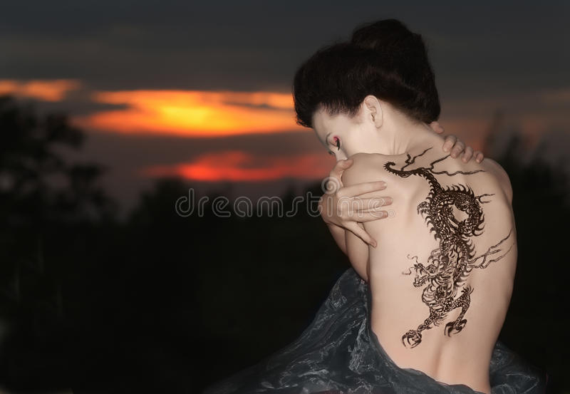 Geisha with dragon tattoo. Sitting on the rocks - looking at rose in sunset time