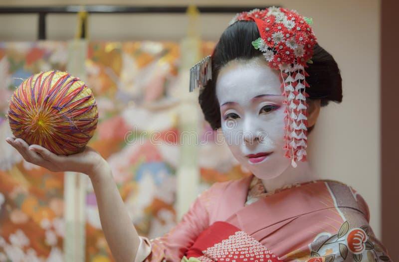 Geisha en el kimono que sostiene una bola tradicional del temari en la mano imagen de archivo libre de regalías
