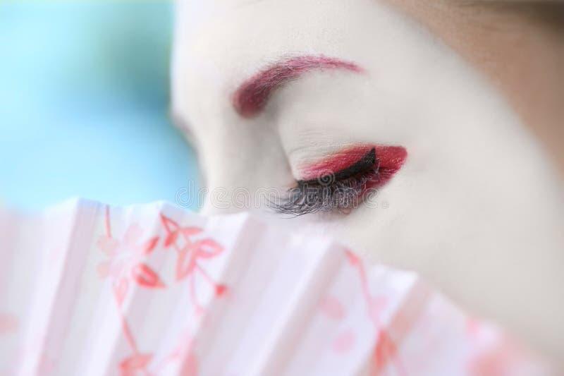 Geisha with fan (closeup, blue background) royalty free stock photos