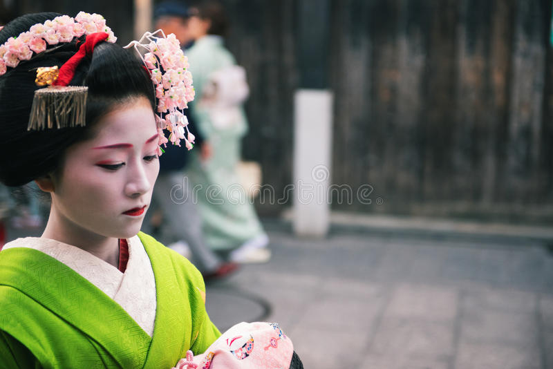 Geisha in Gion. Kyoto, Japan - April 8, 2013: Geisha approaching a tea house in the Gion district of Kyoto. The Geisha in Gion are the highest ranked in Japan royalty free stock photos
