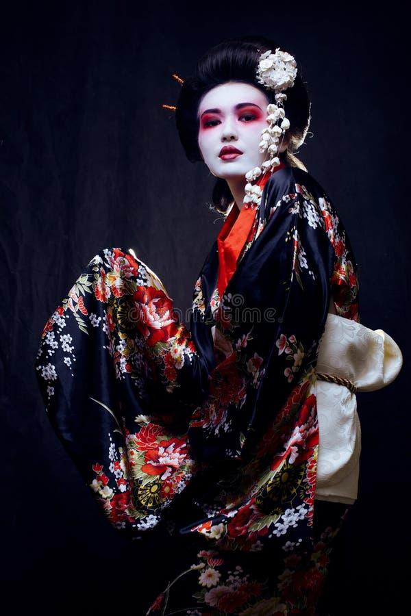 Geisha i kimono på svart royaltyfri foto
