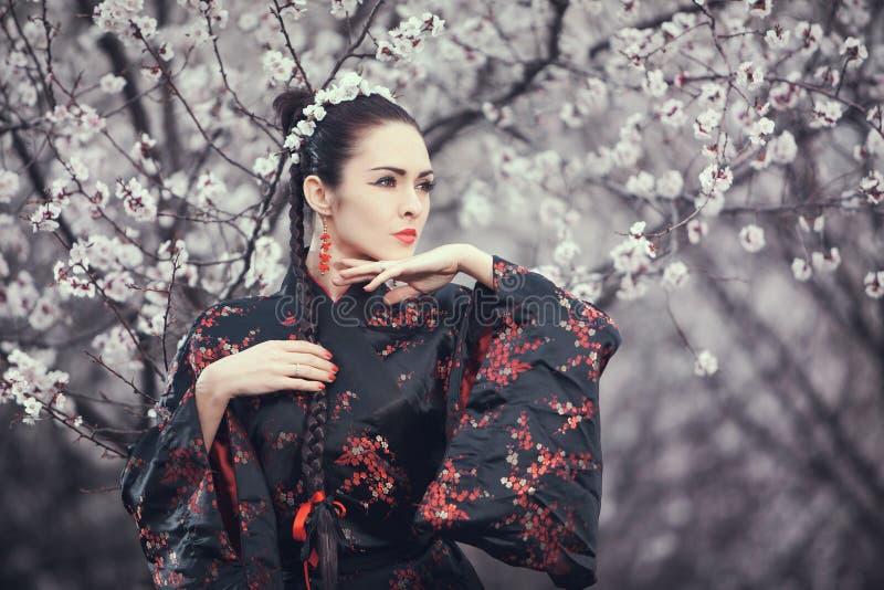 Geisha i röd kimono i sakura royaltyfria foton