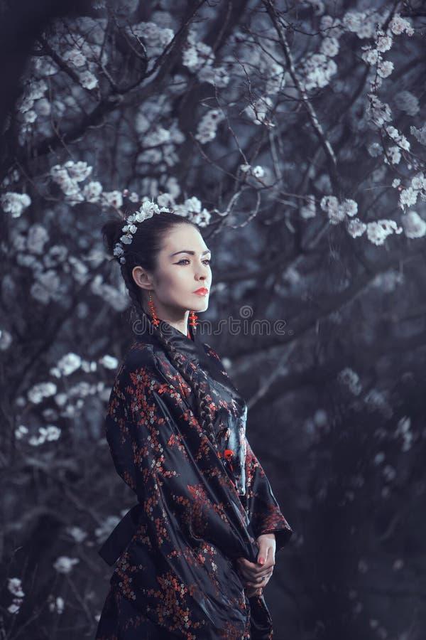 Geisha i röd kimono i sakura royaltyfria bilder