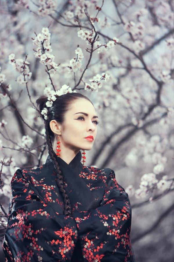 Geisha i röd kimono i sakura royaltyfri foto