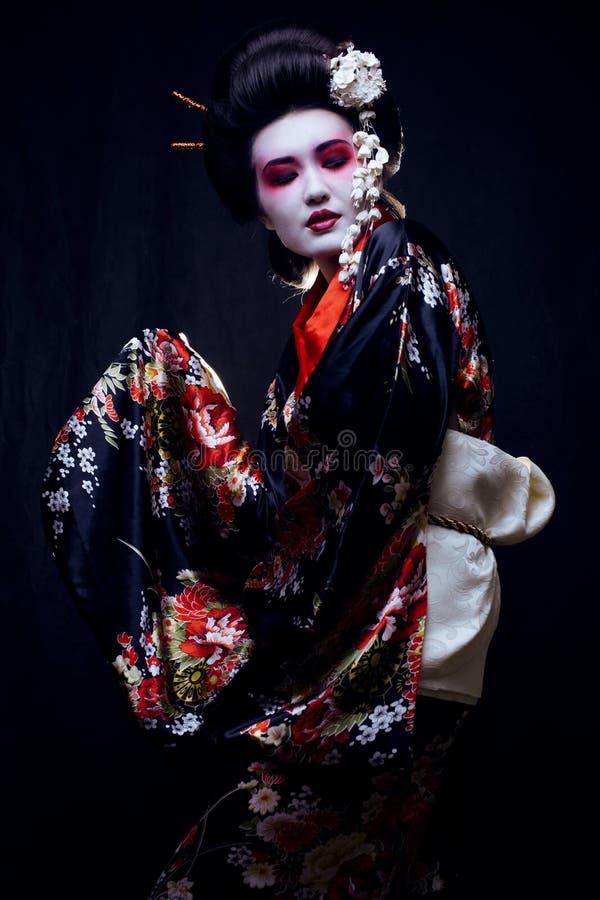 Geisha im Kimono auf Schwarzem stockfotografie