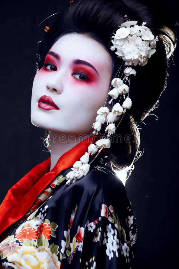 Geisha in kimono on black stock photography