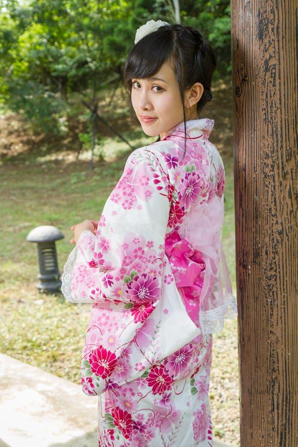 Geisha leaning against wodden pillar royalty free stock photography