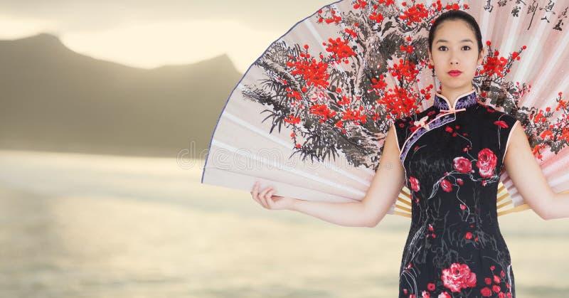 Geisha met reuzeventilator tegen onscherpe gele kustlijn stock afbeeldingen