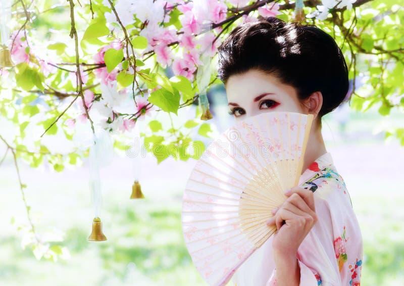 Geisha met ventilator in de tuin stock afbeeldingen