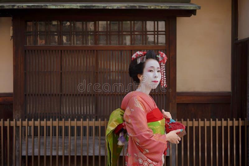 Geisha o maiko en un kimono que camina delante de la puerta de un tradicional fotos de archivo