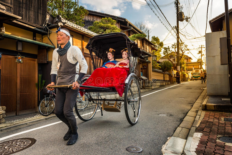 Geishas of Gion. Geishas ride in the back of a rickshaw through the Gion district on December 29, 2015 in Kyoto, Japan royalty free stock images