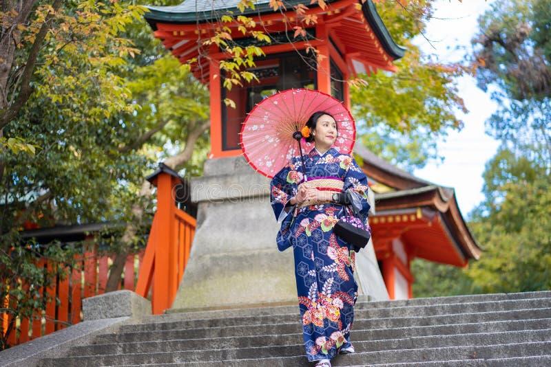 Geishas girl wearing Japanese kimono among red wooden Tori Gate at Fushimi Inari Shrine in Kyoto, Kimono is a Japanese traditional royalty free stock photo