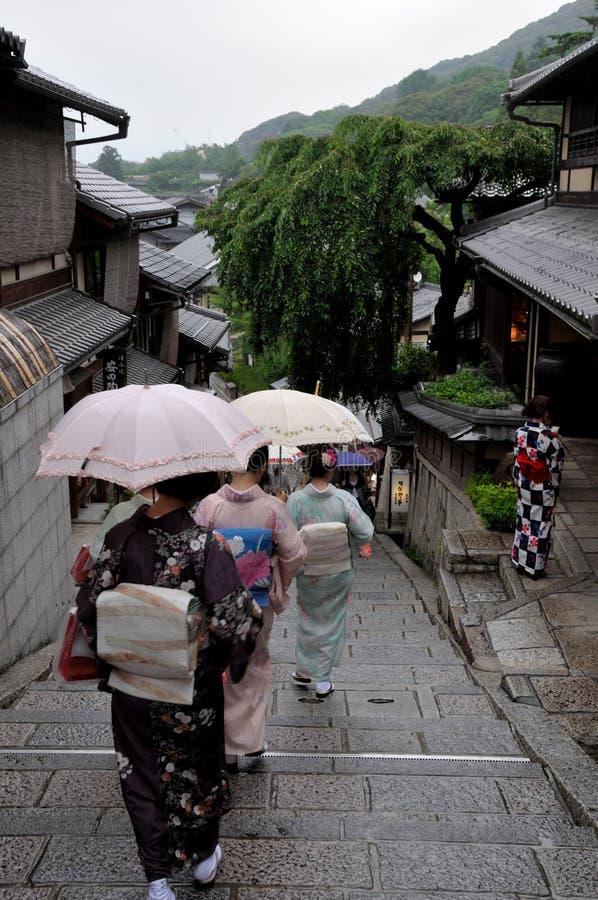 Geishas som går med paraplyet i regnet arkivfoton