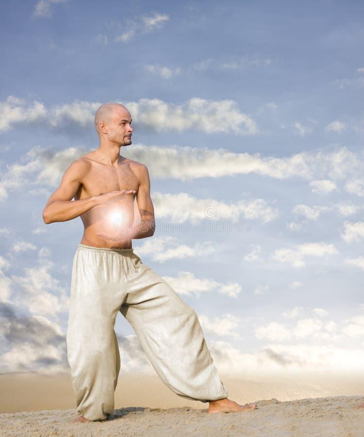Geistiger Mann mit Kugel der Leuchte übt Tai-Chi lizenzfreie stockfotografie