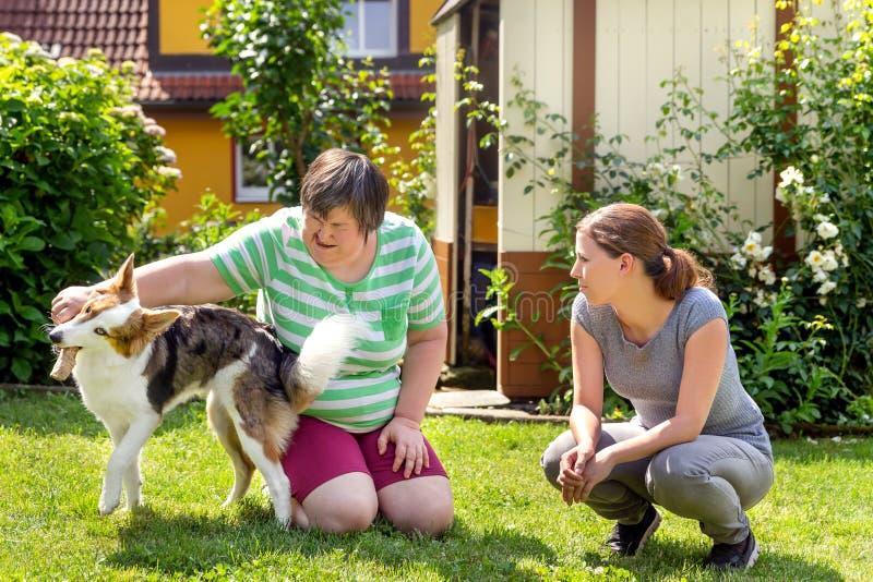 Geistlich - behinderte Frau mit einer zweiten Frau und einem Begleiterhund stockbild