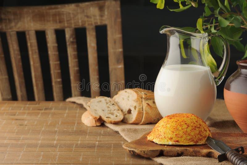 Geitkaas met specerijen, de jachtmes, brood en kruik van mil stock foto