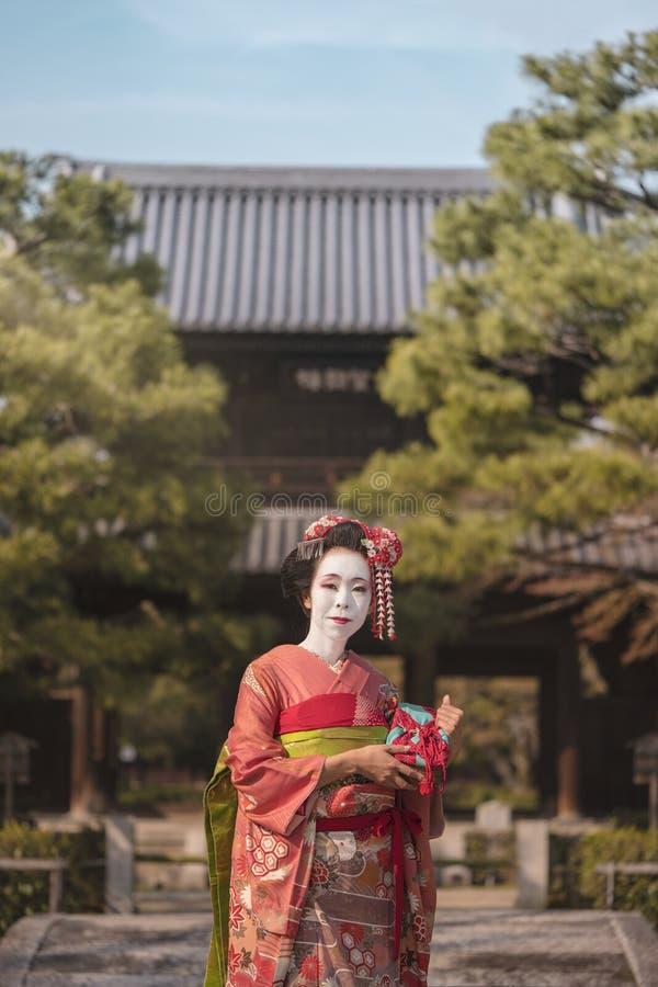 Gejszy dziewczyna w kimonie pozuje w Kyoto na kamiennym moscie przed obraz stock