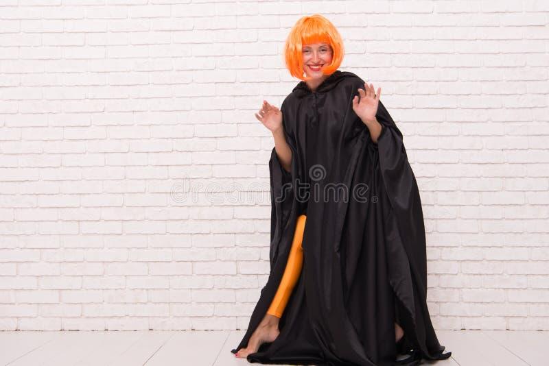 Gek is haar naam Gek meisje dat op witte brickwall glimlacht Partijmeisje met gekke blik Maniermeisje met oranje pruikenhaar stock afbeeldingen