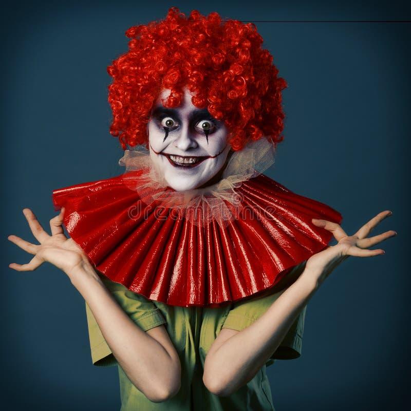 Gek meisje in een kostuum vreselijke clown in een rode pruik en rood vorotkike en groene overhemd op een blauwe achtergrond Hallo stock fotografie
