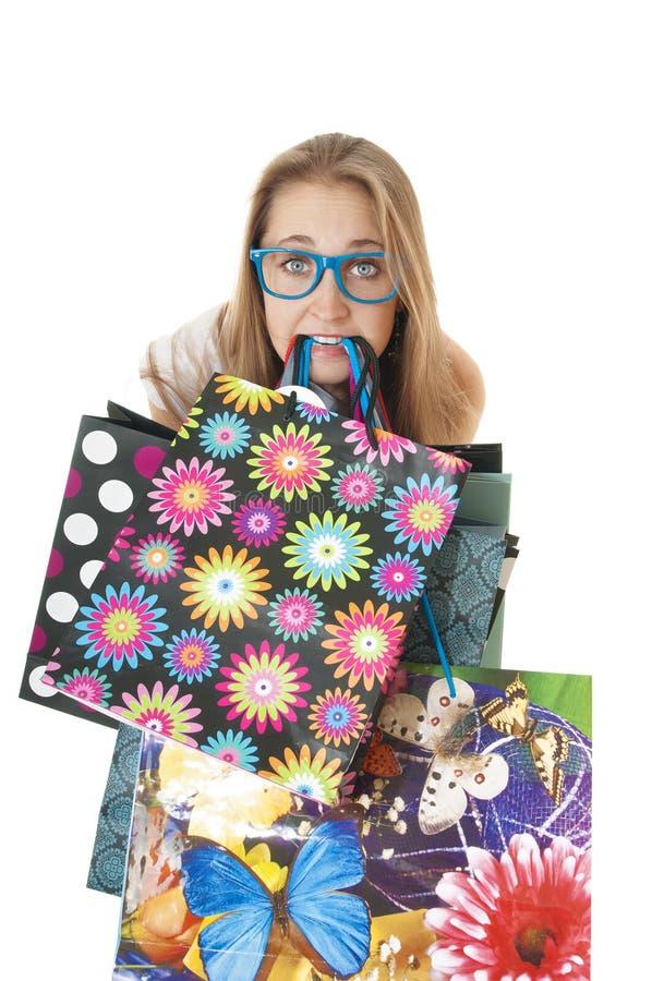 Gek vermakelijk jong meisje met het winkelen giftzakken in de tanden. royalty-vrije stock foto's