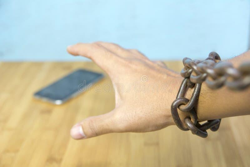 Geketende menselijke hand die slimme telefoon op lijst proberen te vangen stock foto