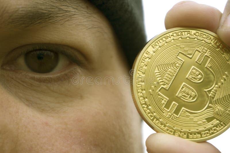 Gekke bitcoinminnaar met een gouden muntstuk in uw hand, grappige mijnwerker met BTC dichtbij het gezicht royalty-vrije stock foto