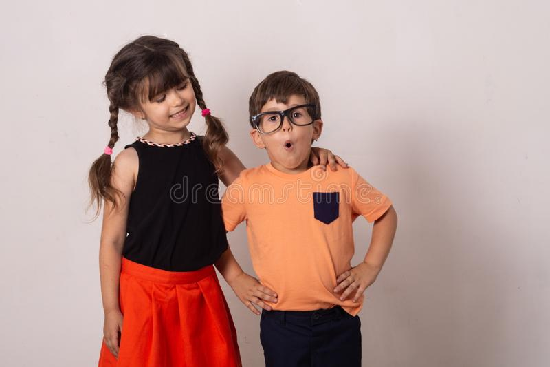 Gekke jonge geitjes! Heldere jonge geitjes Gelukkig die jongen en meisje op grijs wordt geïsoleerd De achtergrond van pretkindere stock fotografie