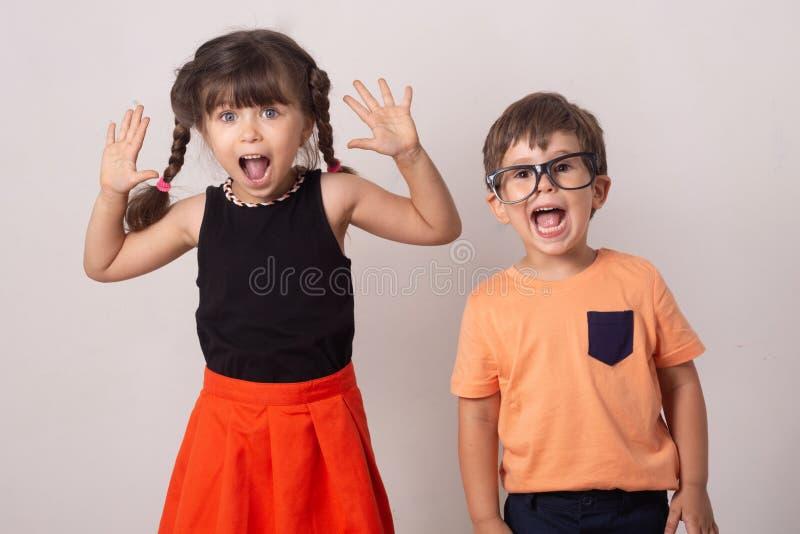 Gekke jonge geitjes! Heldere jonge geitjes Gelukkig die jongen en meisje op grijs wordt geïsoleerd De achtergrond van pretkindere stock foto's