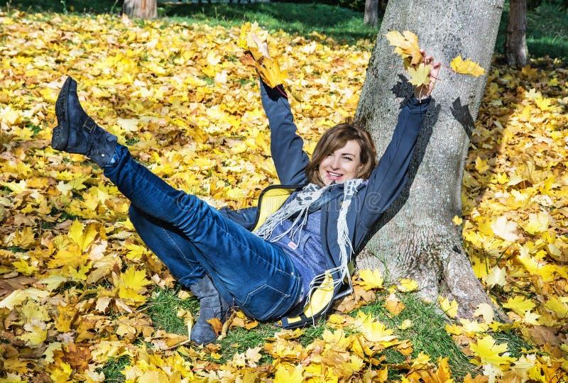 Gekke jonge vrouw die gele bladeren in de herfst, seizoengebonden lif werpen royalty-vrije stock foto's