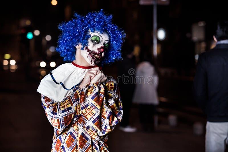 Gekke lelijke grunge kwade clown in stad op Halloween die mensenschok maken en doen schrikken royalty-vrije stock foto