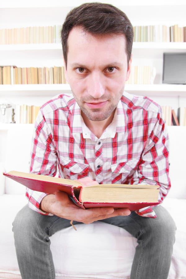 Gekke mannelijke student of professor met boek in handen royalty-vrije stock afbeelding
