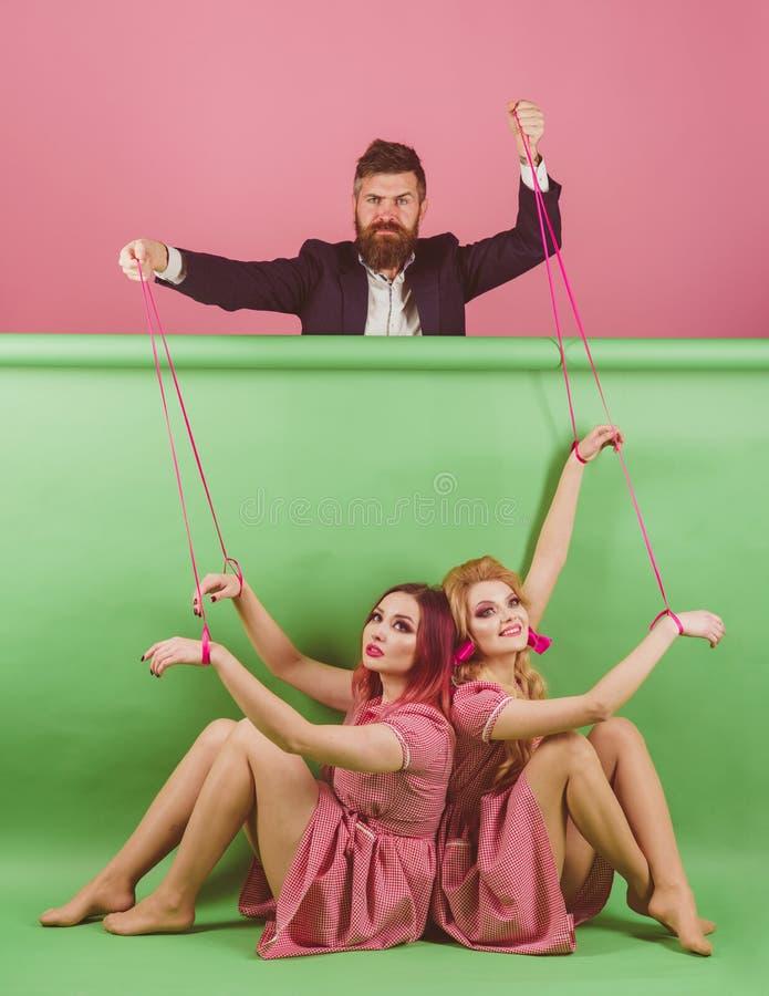 Gekke meisjes en mens op roze Halloween vakantie en poppen overheersing en afhankelijkheid Creatief idee Portret van twee vrouwen royalty-vrije stock afbeelding