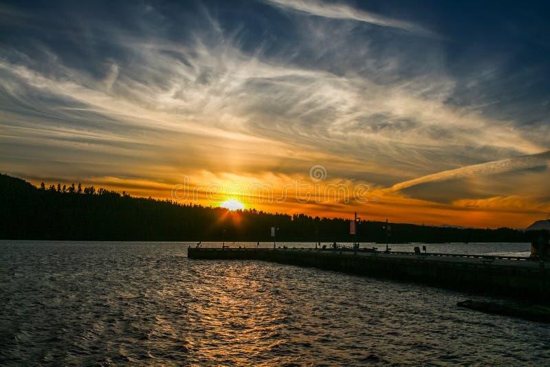 Gekke oranje zonsondergang op de bewolkte hemel stock afbeelding