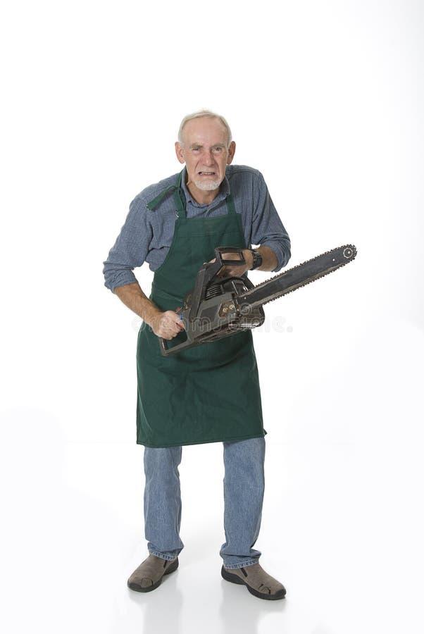 Gekke oude mens met kettingzaag stock foto's