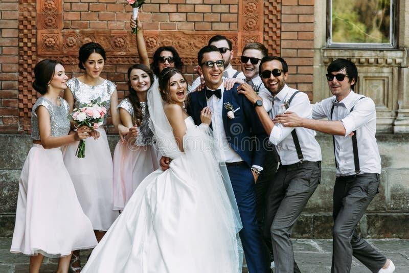 Gekke paar en bruidsmeisjes met erachter groomsmen stock foto