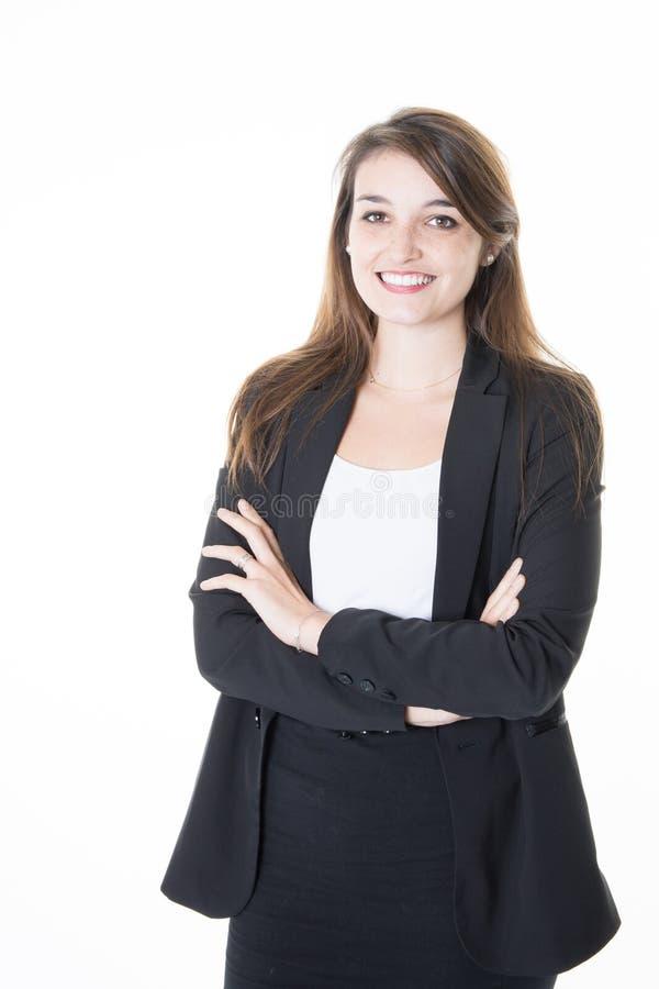 Geklede bedrijfsvrouw die de camera met haar gekruiste wapens onderzoeken terwijl status voor witte achtergrond royalty-vrije stock foto's